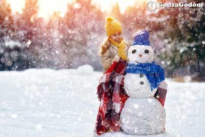 Зимой идет снег, девочка лепит снеговика